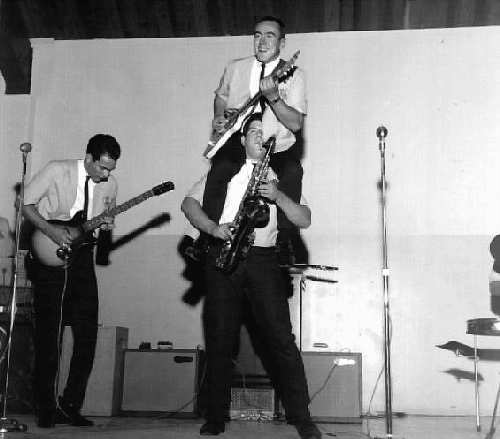 Norsemen - Don Nathman to the left playing the guitar, then Jim Coleman playing guitar whilst riding on Mike Scheil's shoulders; North Marion High School gymnasium. - Photo Courtesy of David Higginbotham